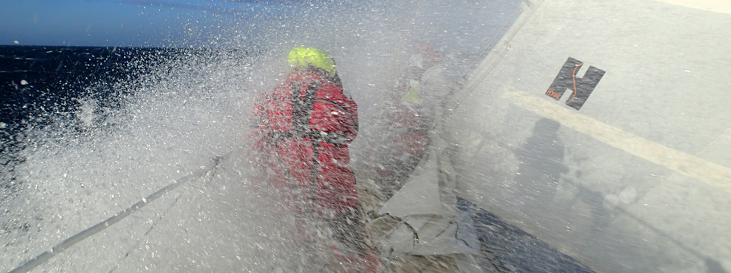 Crew member getting wet on the bow during the race to Brisbane, Australia
