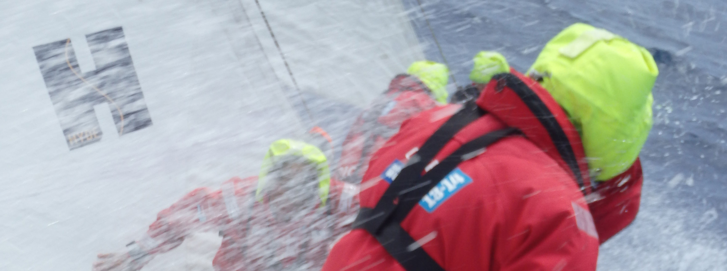 Picture of crew in tough weather conditions on the last Clipper Race, with Hyde Sails logo.