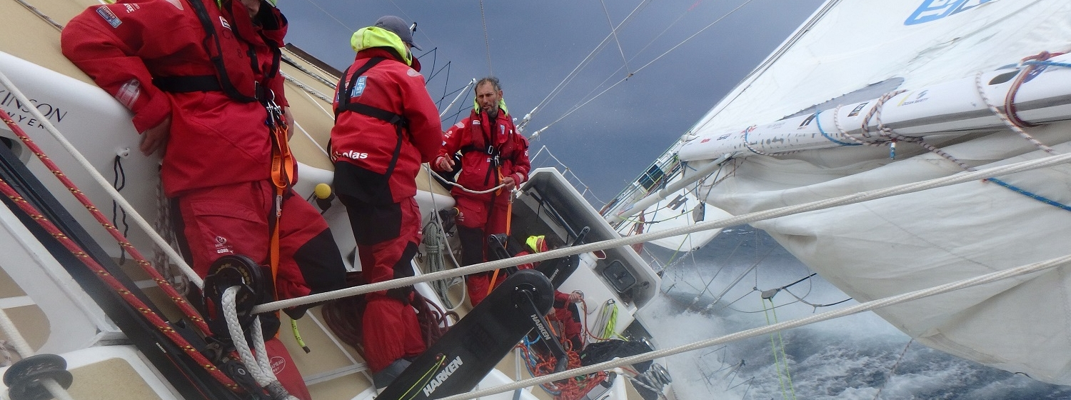 Crew shown standing at an angle in rough weather as Pacific Ocean front takes force