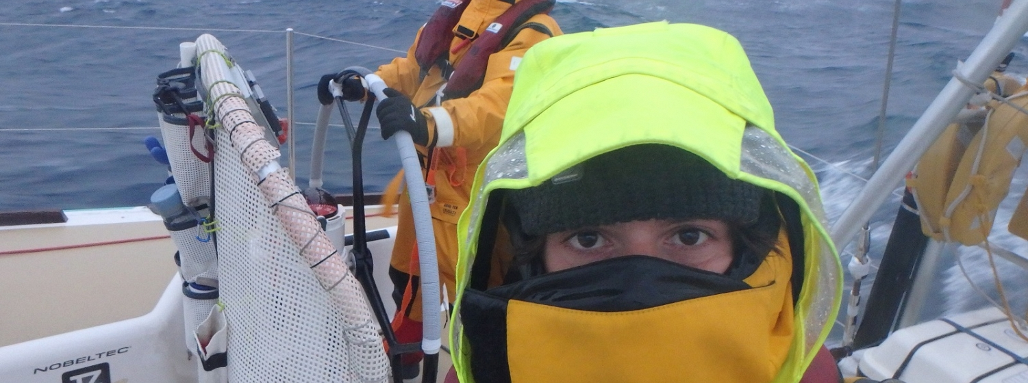 Crew member looking into camera in full foulies with just eyes showing