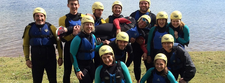 Skipper Wendo shown being raised by her team after a raft building challenge in the Peak District