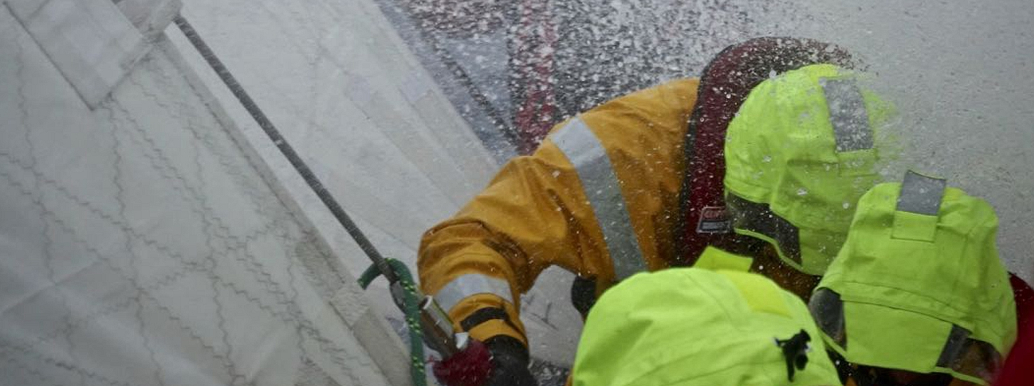 Waves crash over 3 crew members at the bow